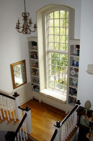 Traditional Staircase with Built-in bookshelf, Arched window, curved staircase, High ceiling, Chandelier, Hardwood floors