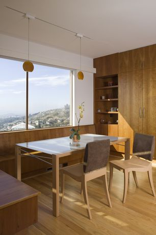Contemporary Dining Room with Hardwood floors, Pendant light, Built-in bookshelf, Standard height, picture window