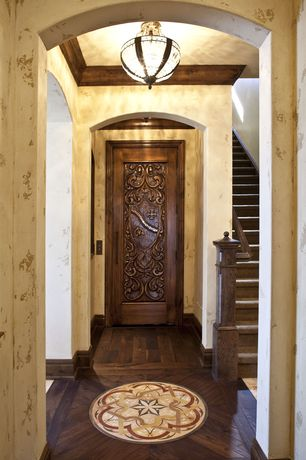 Mediterranean Hallway with specialty door, flush light, interior wallpaper, Crown molding, High ceiling, Hardwood floors