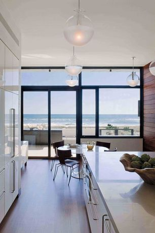 Contemporary Dining Room with sliding glass door, picture window, Pendant light, Laminate floors, Transom window