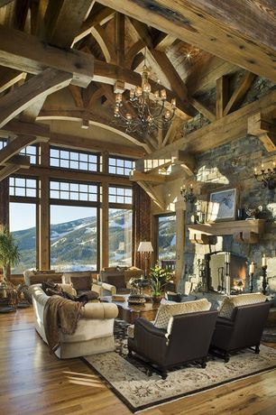 Rustic Living Room with Transom window, Large picture windows, Chandelier, Wood mantel, Hardwood floors, Area rug