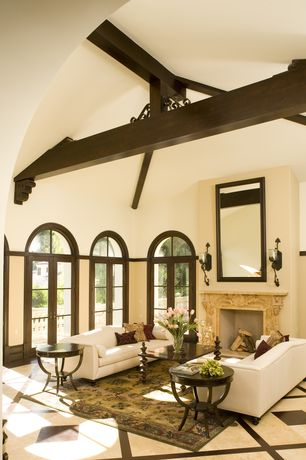 Mediterranean Living Room with High ceiling, Arched window, simple marble tile floors, French doors, Cement fireplace