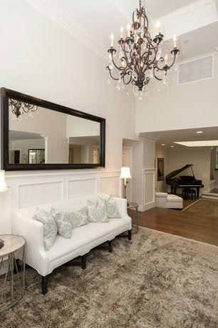 Traditional Entryway with specialty door, Crown molding, High ceiling, Wainscotting, Chandelier, Hardwood floors