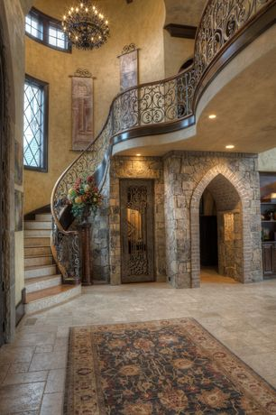 Mediterranean Entryway with Exposed beam, Chandelier, travertine floors, Hanging tapestry, specialty door, Wine cellar door