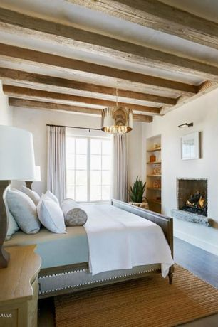 Eclectic Master Bedroom with Hardwood floors, Standard height, Exposed beam, Cement fireplace, Built-in bookshelf, Casement