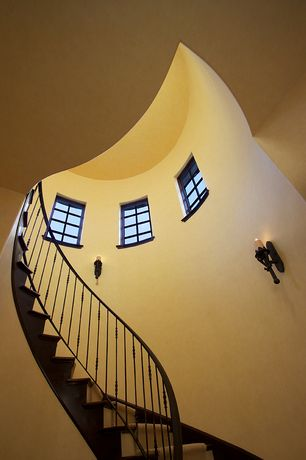 Mediterranean Staircase with Wall sconce, Cathedral ceiling, Carpet