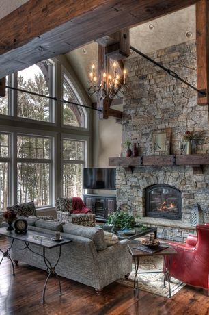 Rustic Living Room with Neiman marcus massoud red leather chair, Fieldstone fireplace, stone fireplace, Exposed beam