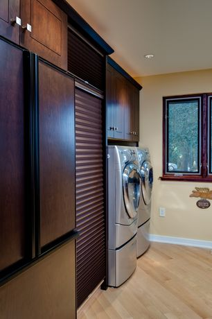 Contemporary Laundry Room with Front loading washer/dryer with pedestal, Paint, can lights, Diagonal wood flooring, Casement