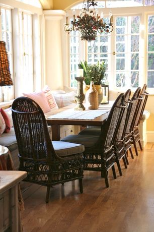 Cottage Dining Room with Chandelier, Hardwood floors, Arched window, Window seat