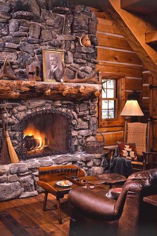 Rustic Living Room with Exposed beam, double-hung window, Accent pillows, Hardwood floors, Exposed stone wall, Fireplace