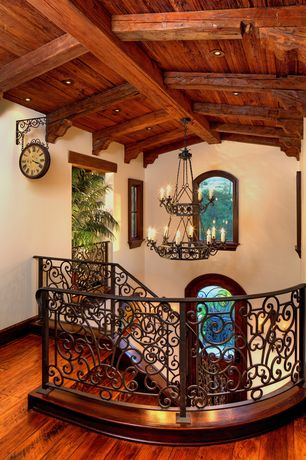 Mediterranean Staircase with Chandelier, Exposed beam, Arched window, Vintage wall mount clock, Hardwood floors, can lights
