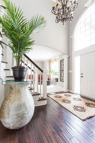 Traditional Entryway with Chandelier, six panel door, Columns, High ceiling, Transom window, Hardwood floors