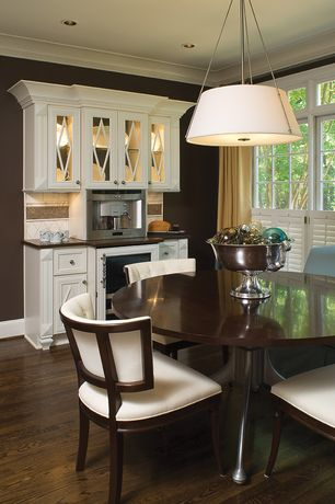 Modern Dining Room with Hardwood floors, can lights, Paint 1, Casement, Standard height, Built-in bookshelf, Crown molding