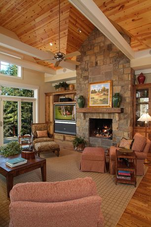 Country Living Room with High ceiling, stone fireplace, Transom window, Exposed beam, Hardwood floors, Ceiling fan