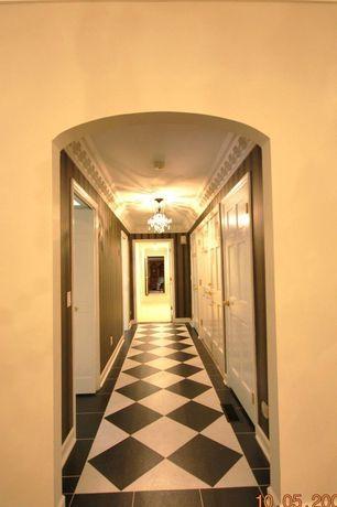 Eclectic Hallway with terracotta tile floors, Chandelier, Columns