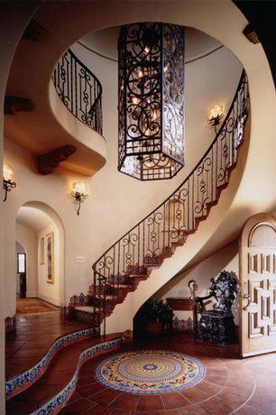 Mediterranean Entryway with specialty door, High ceiling, Chandelier, terracotta tile floors, Paint