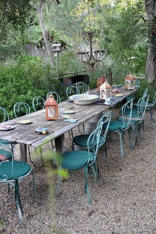 Rustic Patio with Outdoor kitchen, Fence, Gravel path, Vintage metal candelabra, Decorative metal lantern, Cushion
