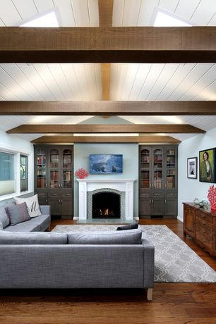 Traditional Living Room with High ceiling, Hardwood floors, Built-in bookshelf, Exposed beam, stone fireplace, Skylight