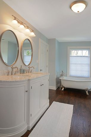 Traditional Master Bathroom with wall-mounted above mirror bathroom light, Inset cabinets, Travertine counters, Bathtub