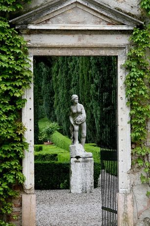 Traditional Landscape/Yard with Classical garden sculptures, Shrubs, Ivy, Pathway, Gate, Small rock ground cover, Fence