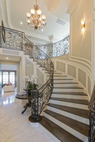 Traditional Staircase with curved staircase, Wainscotting, Hardwood floors, Chandelier, High ceiling, Wall sconce