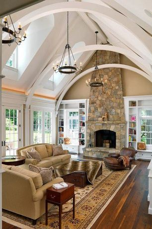 Traditional Living Room with French doors, Cathedral ceiling, Chandelier, Built-in bookshelf, Hardwood floors, Exposed beam