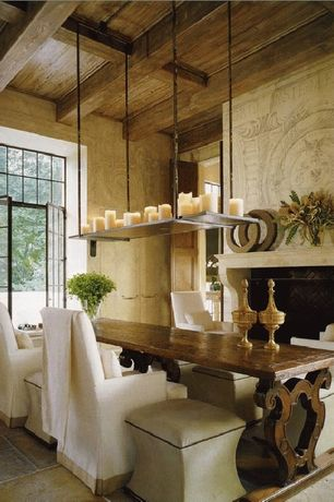 Mediterranean Dining Room with Standard height, Casement, limestone tile floors, Fireplace, specialty door, stone tile floors