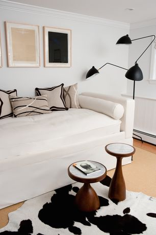 Contemporary Guest Bedroom with Spinneybeck cowhide rug, Serge mouille three-arm floor lamp, Crown molding, Laminate floors