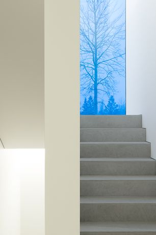 Contemporary Staircase with High ceiling, Concrete floors