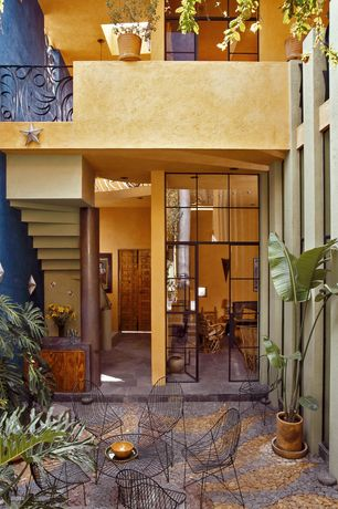 Mediterranean Patio with exterior stone floors, French doors, Transom window