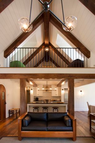 Traditional Great Room with flat door, Wall sconce, Hardwood floors, Cathedral ceiling, Columns, Exposed beam, Skylight, Loft
