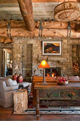 Rustic Living Room with Hardwood floors, Exposed beam, flush light, Petrified wood stump mixed side table, stone fireplace