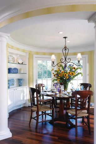 Traditional Dining Room with Crown molding, Columns, Glass panel door, Chandelier, Hardwood floors