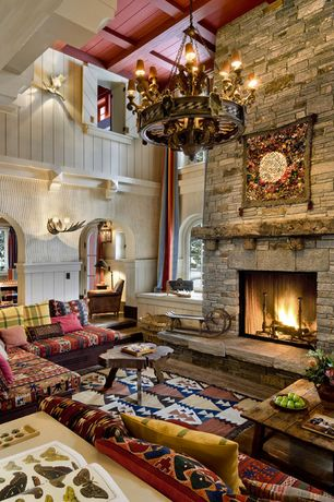 Country Living Room with Chandelier, Frank Armich Treetrunk Coffee Table, stone fireplace, Wall sconce, Crown molding