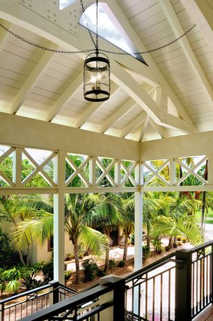 Tropical Porch with Screened porch, exterior stone floors, Fence