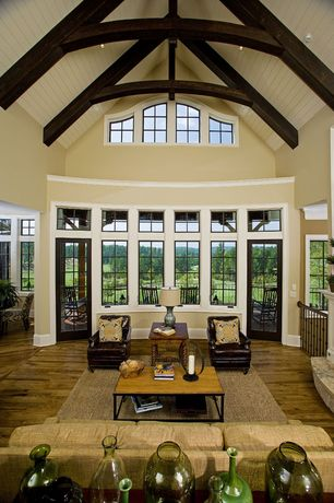 Traditional Great Room with French doors, High ceiling, Safavieh jax coffee table, Hardwood floors, Transom window