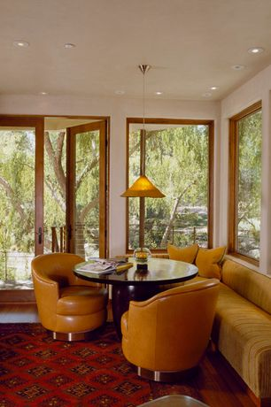Contemporary Dining Room with French doors, Hardwood floors, Window seat, Pendant light