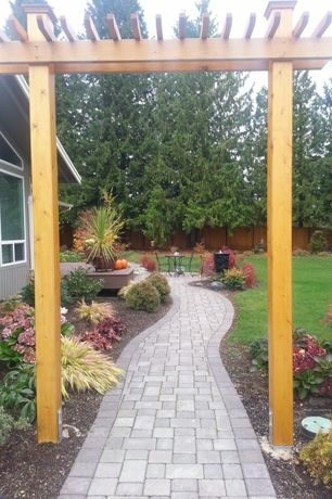 Traditional Landscape/Yard with Pathway, exterior stone floors, Fence, Arbor