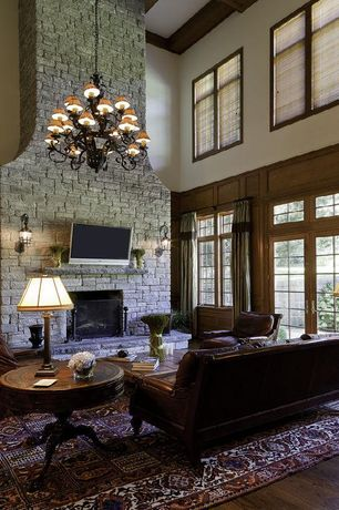 Traditional Living Room with stone fireplace, Chandelier, Fireplace, Exposed beam, Wall sconce, Hardwood floors, Casement