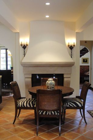 Mediterranean Dining Room with stone fireplace, can lights, Fireplace, terracotta tile floors, Wall sconce, Standard height