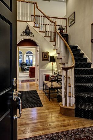 Traditional Entryway with Hardwood floors, Wainscotting, specialty door, High ceiling
