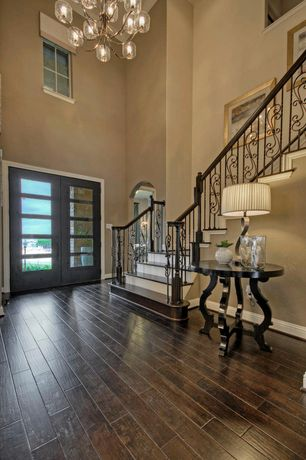 Modern Entryway with High ceiling, Console table, Wrought iron railing, Paint, Hardwood floors, Crown molding, Chandelier