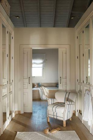 Traditional Closet with bedroom reading light, Exposed beam, specialty door, Standard height, Hardwood floors