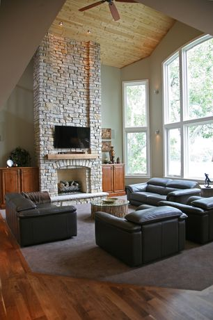 Contemporary Living Room with Casement, Fireplace, Ceiling fan, brick fireplace, can lights, Hardwood floors, Wall sconce
