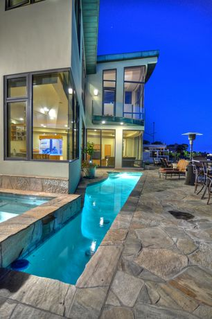 Contemporary Swimming Pool with exterior stone floors, Lap pool
