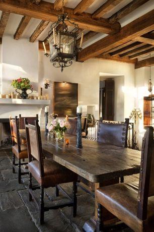 Mediterranean Dining Room with Chandelier, Exposed beam, soapstone tile floors, Standard height, stone tile floors