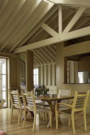 Cottage Dining Room with Columns, Hardwood floors, High ceiling, Exposed beam, Built-in bookshelf, Wall sconce