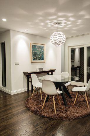 Contemporary Dining Room with can lights, Chandelier, sliding glass door, Standard height, Hardwood floors