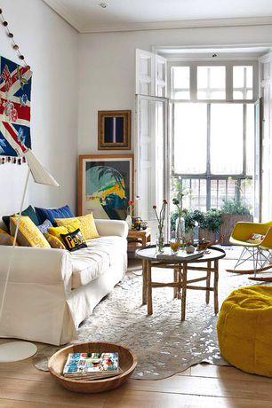 Eclectic Living Room with Herman Miller Eames Molded Plastic Rocker, Hardwood floors, Transom window, French doors