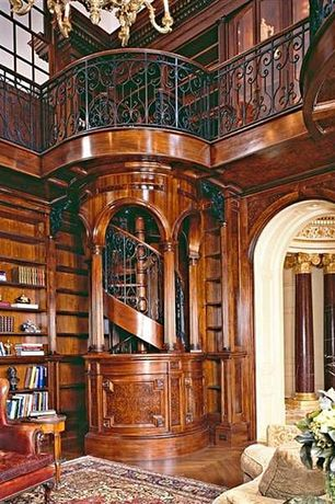 Traditional Home Office with Built-in bookshelf, Hardwood floors, Vintage leather gentleman club armchair, Arched doorway